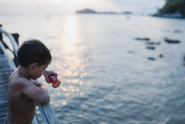 Boy on a pier at a beach in Malaysia at sunset
