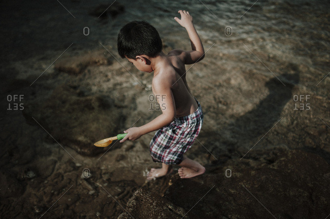 Little boy playing on rocks in tide on beach in Malaysia