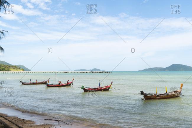 Phuket, Thailand - June 17, 2012: Traditional boats anchored along the shore of Rawai Beach
