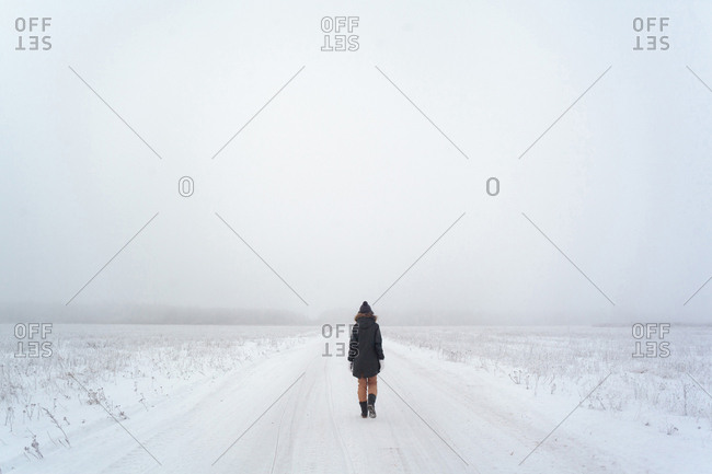 Rear view of woman walking on snowy field against sky during foggy weather