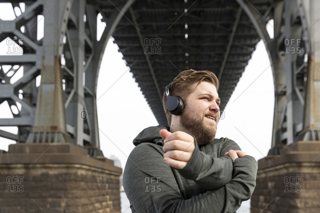 Young man stretching arms while listening music on headphones below Williamsburg Bridge in city