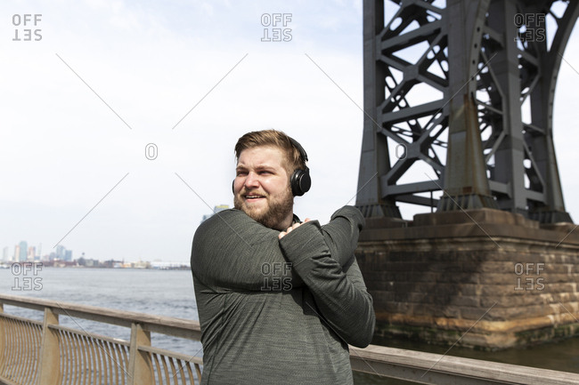 Young man stretching arms while listening music on headphones by Williamsburg Bridge in city