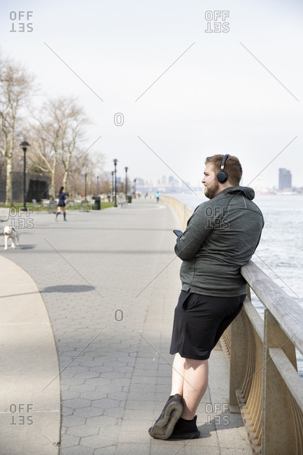 Full length of overweight man listening music on headphones while standing by river in city