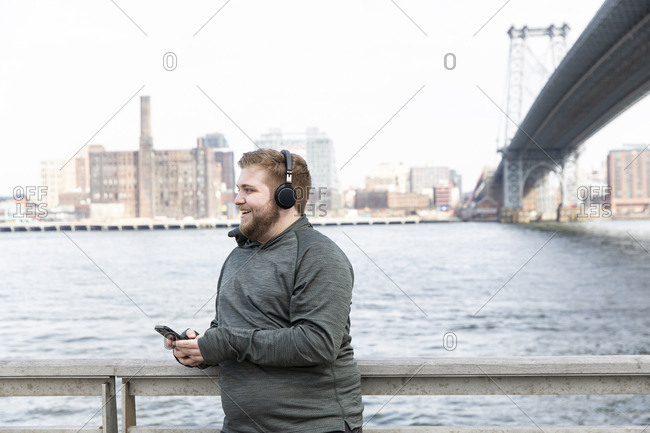 Smiling overweight man listening music on headphones while standing by river against Williamsburg Bridge in city