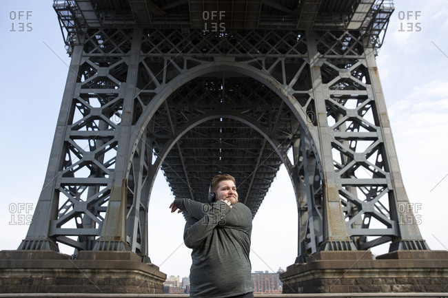 Overweight man stretching arms while standing below Williamsburg Bridge in city