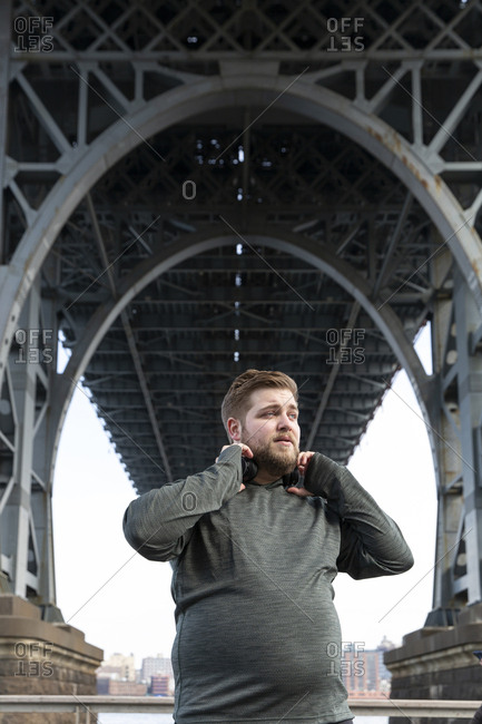 Overweight man holding headphones while standing below Williamsburg Bridge in city