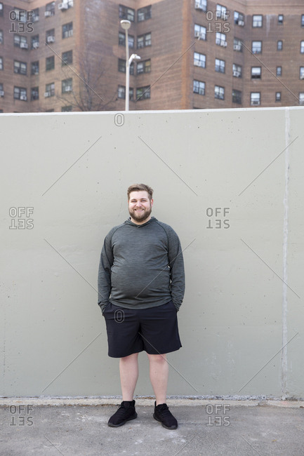 Full length portrait of overweight man with hands in pockets standing against wall in city