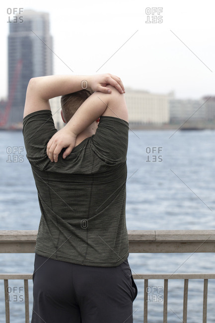 Rear view of overweight man stretching arms behind back while standing on bridge by river in city