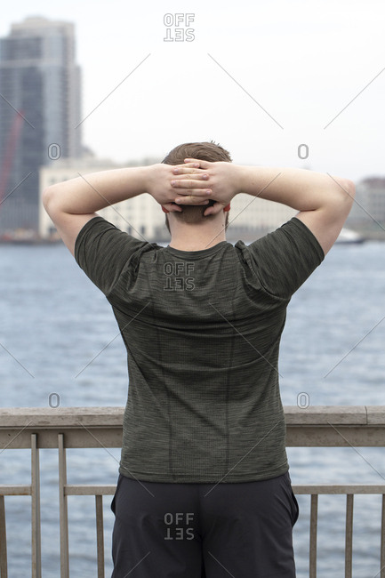 Rear view of overweight man with hands behind head exercising on bridge by river in city
