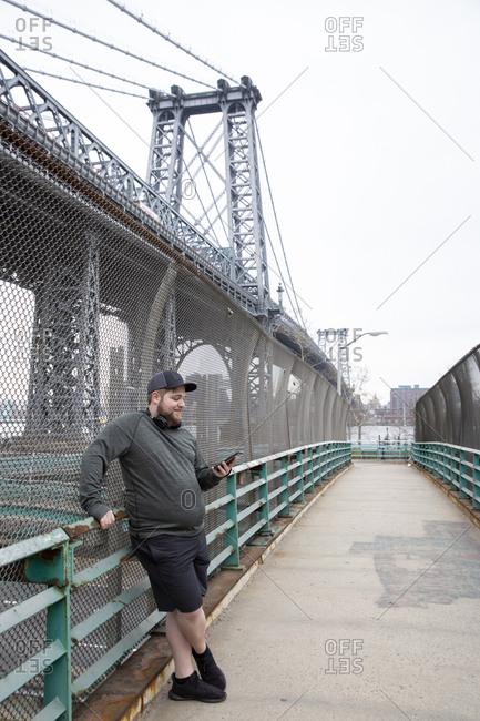 Full length of overweight man using smart phone while standing against Williamsburg Bridge in city