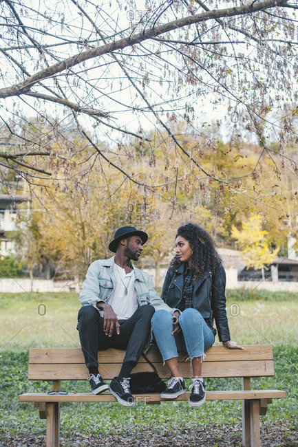 Romantic couple looking at each other while sitting on bench against sky in park