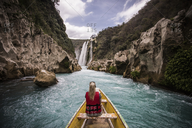 Rear view of woman sitting in boat on river by mountains against waterfall