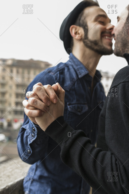 Happy gay couple kissing while standing in balcony against sky