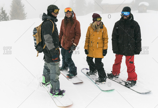 Full length of smiling friends standing with snowboards on snow during snowfall