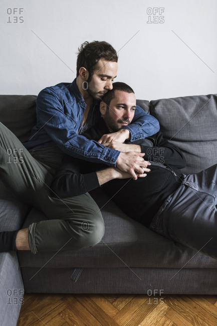 Gay couple romancing while sitting on sofa at home