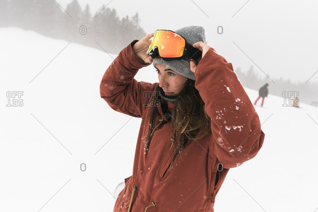 Woman wearing ski goggles while standing on snowy field during foggy weather