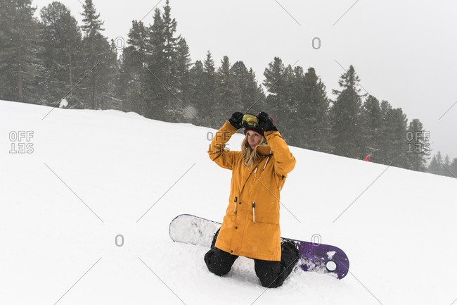 Woman wearing ski goggles while snowboarding on snowy field during foggy weather