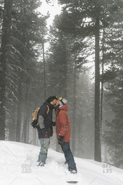 Side view of couple kissing while standing on snowy field against trees during foggy weather