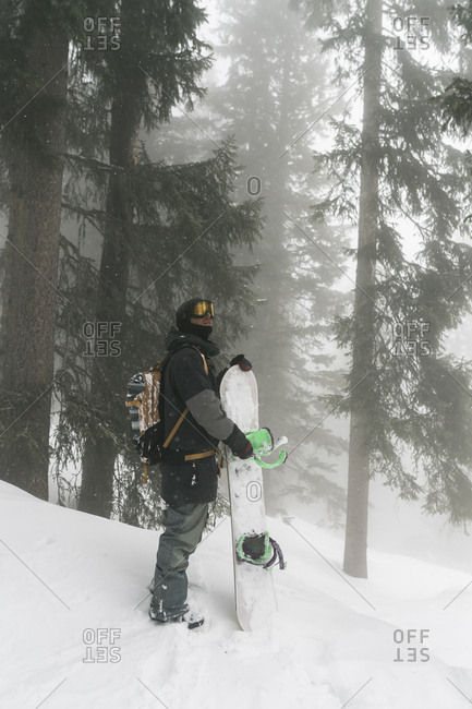 Full length of man holding snowboard while standing on snowy field at forest during foggy weather