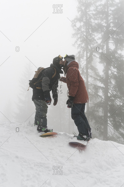 Side view of couple with snowboards kissing while standing on snowy field against trees during foggy weather