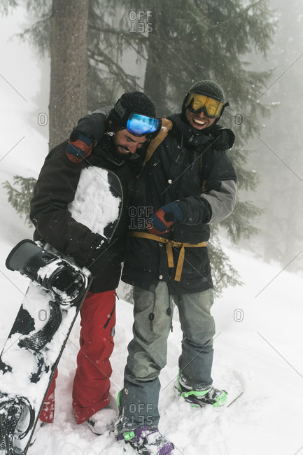 Full length of cheerful friends with snowboards standing on snowy field at forest during foggy weather