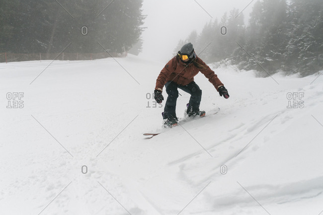 Carefree woman snowboarding on snow during foggy weather