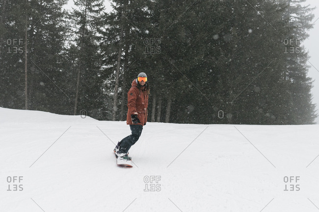 Full length of woman snowboarding against trees during snowfall