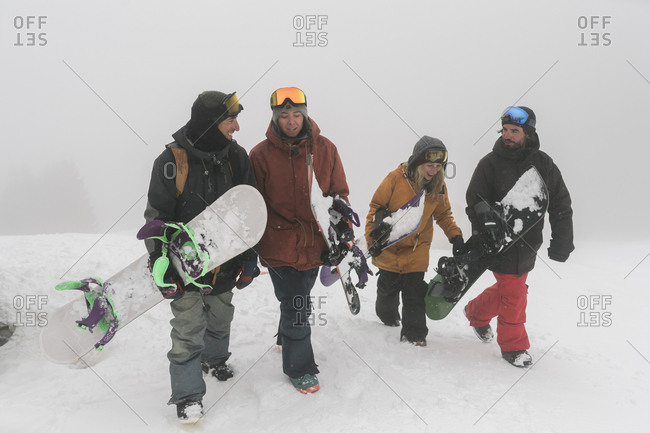 Friends with snowboards walking on snow during foggy weather