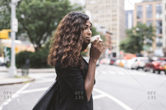 Side view of businesswoman drinking coffee while standing on city street