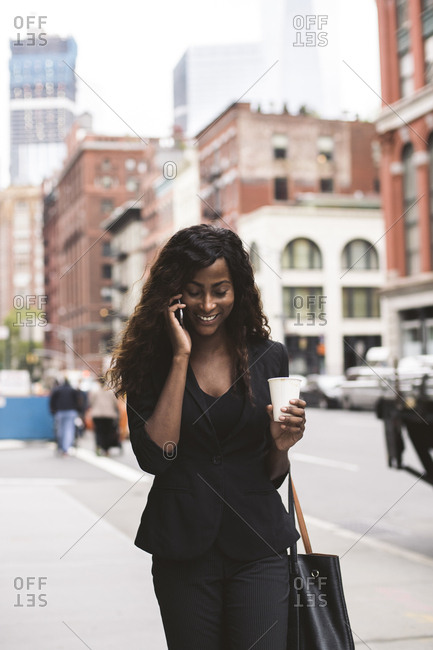 Businesswoman with coffee talking on mobile phone while walking on sidewalk in city