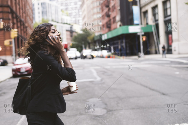 Side view of businesswoman with coffee talking on smart phone while walking on city street