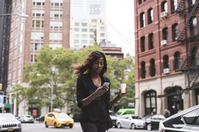 Businesswoman with coffee using smart phone while walking on city street