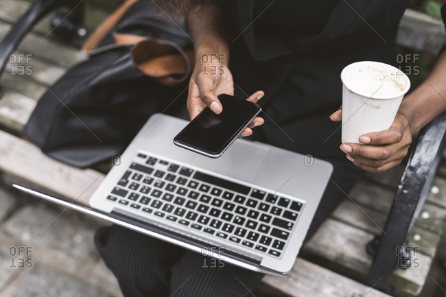 Midsection of businesswoman with laptop computer using smart phone while sitting on bench in city