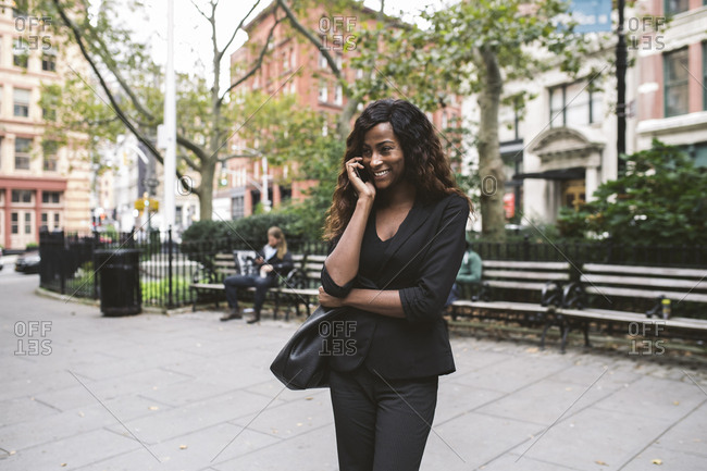 Businesswoman talking on smart phone while standing on city street