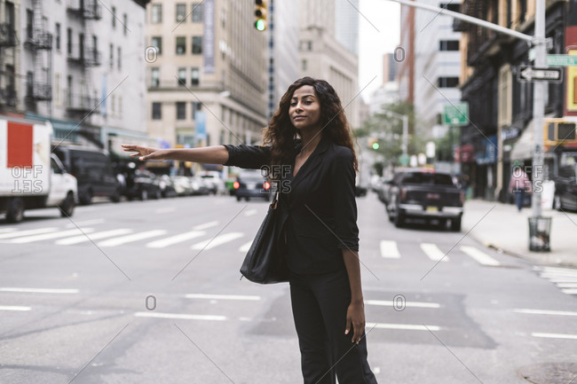 Businesswoman hailing while standing on city street