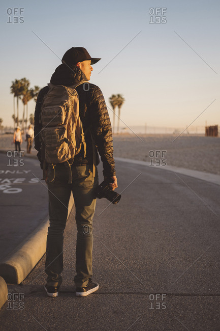 Rear view of man with backpack and camera standing on road by beach against clear sky during sunset