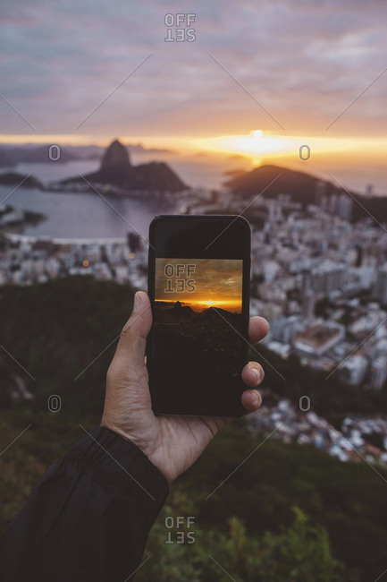 Cropped hand of man photographing city by sea against cloudy sky during sunset