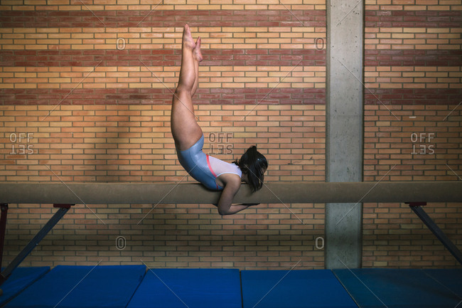Side view of female gymnast exercising on balance beam against wall at gym