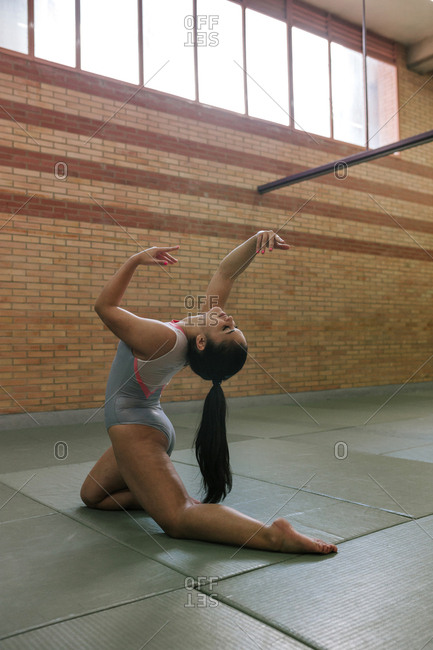 Full length of female gymnast exercising at gym