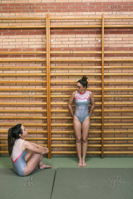 Female gymnasts wearing leotards while talking in gym