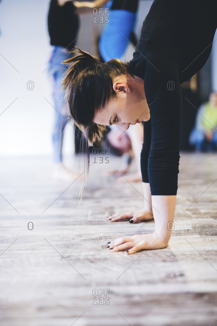 Woman practicing handstand while instructor assisting man in background at yoga studio