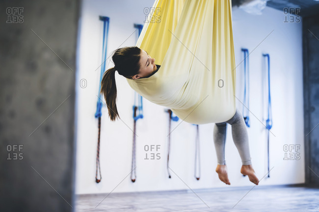 Young woman hanging in hammock while practicing yoga at gym