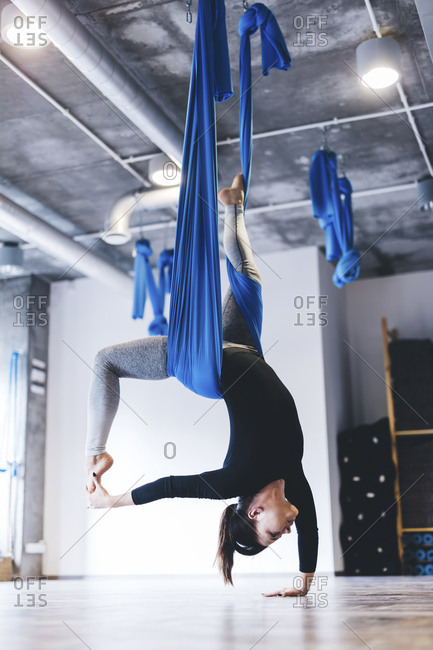 Full length of young woman practicing aerial yoga while hanging from hammock in gym