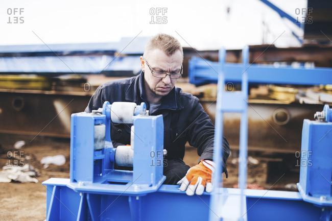 Serious manual worker making machinery at shipyard