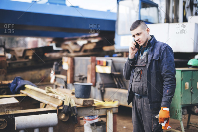 Manual worker answering smart phone while standing at shipyard