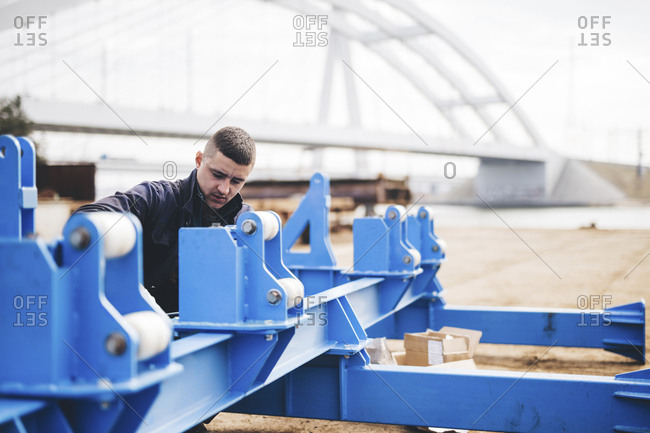 Manual worker making machinery at shipyard against bridge in city