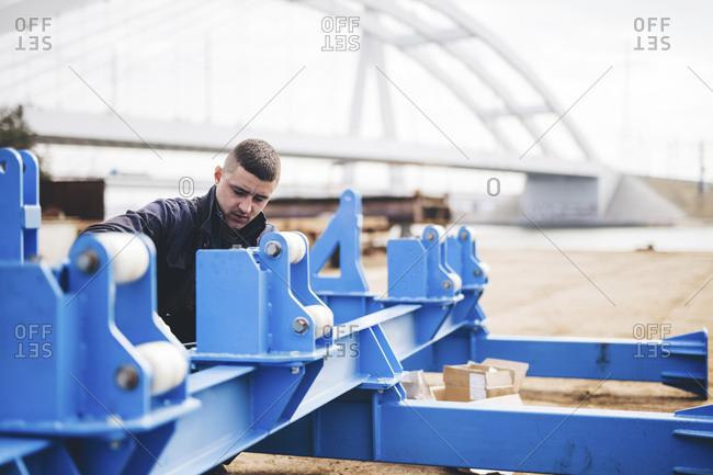 Manual worker making machinery at shipyard against bridge in city