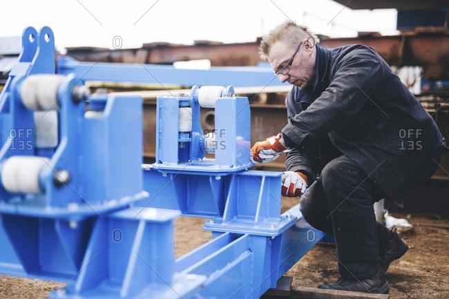 Full length of serious manual worker making machinery at shipyard