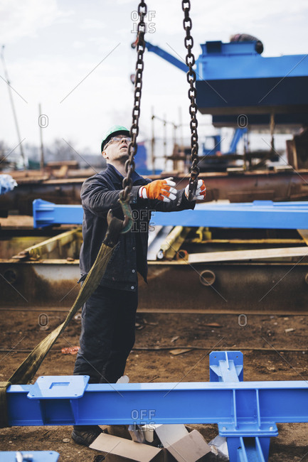 Manual worker looking up while holding metallic chain at shipyard