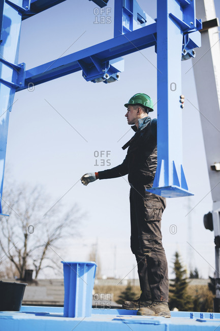 Full length of manual worker standing on machinery while working at shipyard during sunny day
